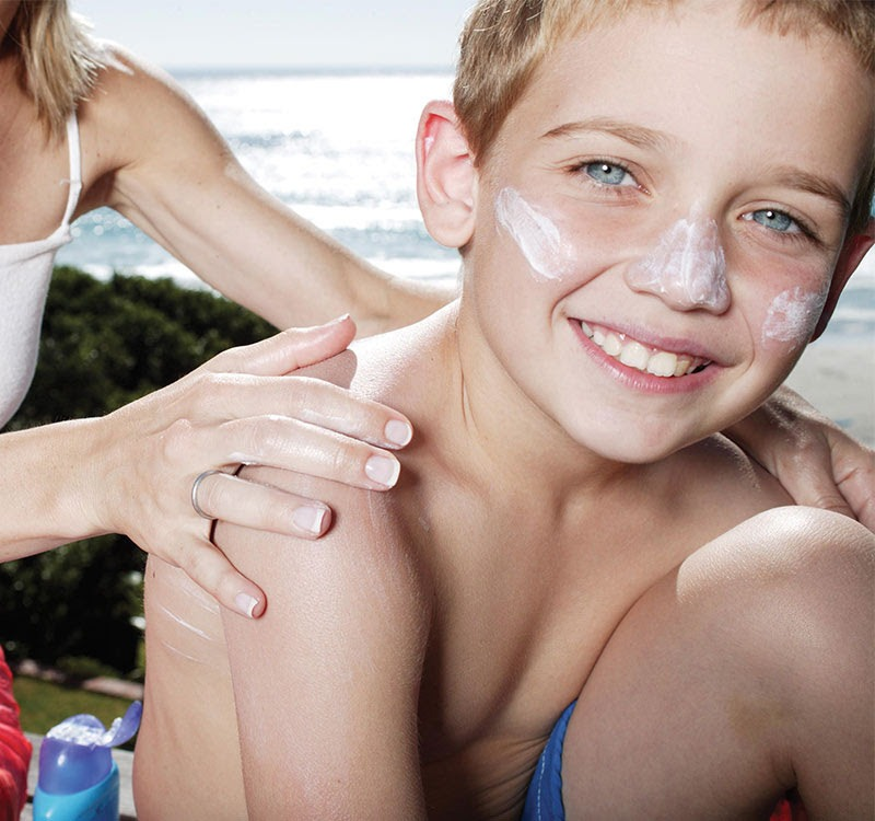 boy with sun lotion on nose and cheeks