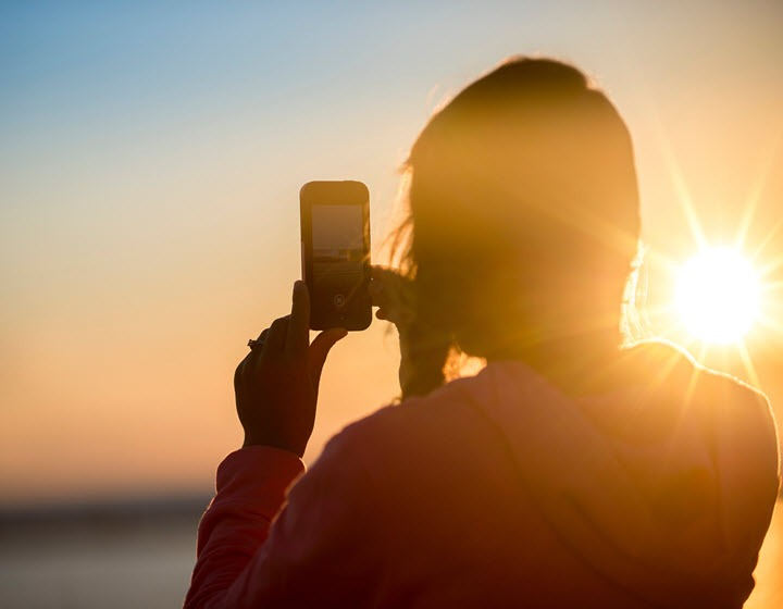 silhouette of girl with mobile in the sun